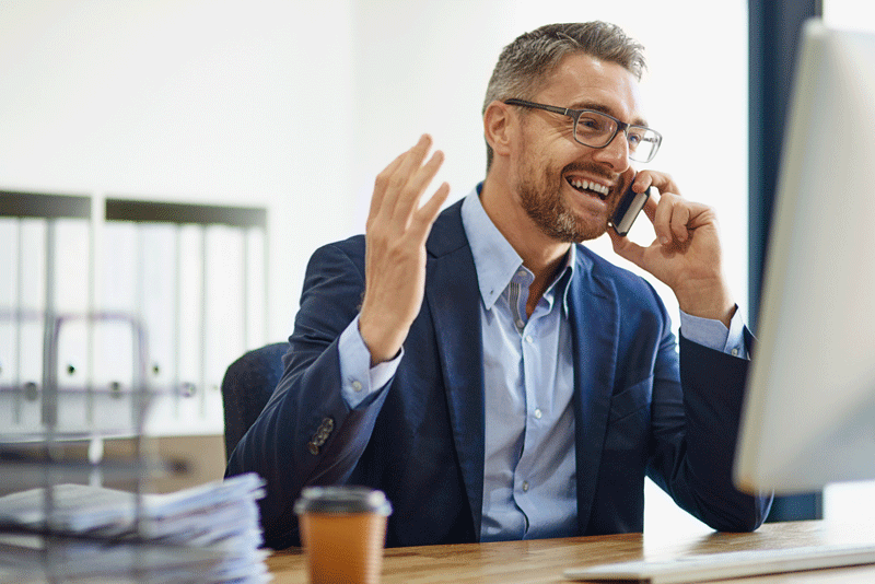 smiling middle aged man on phone in front of computer