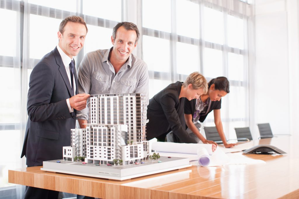 two men with building model smiling