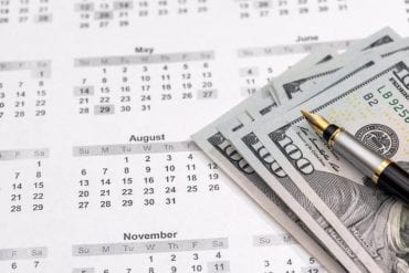 Money and pen on top of calendar