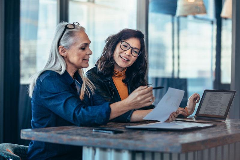 Two businesswomen looking at paperwork